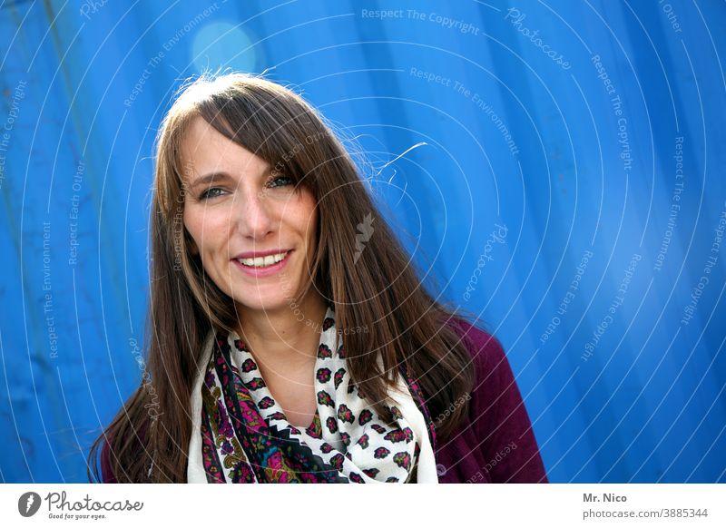 Lächelnde junge Frau vor blauem Hintergrund feminin langhaarig brünett schön Zufriedenheit Freundlichkeit natürlich Sympathie Porträt Blick in die Kamera Licht