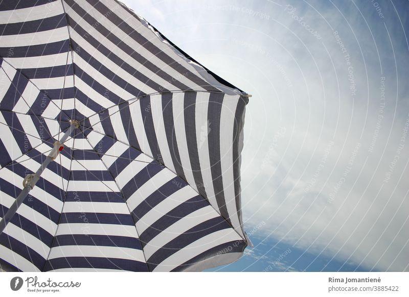 Ein Sonnenschirm gegen den klaren Himmel am Strand im Sommer Regenschirm Urlaub MEER reisen Feiertage blau Sand Erholung ruhen Urlaubshintergrund