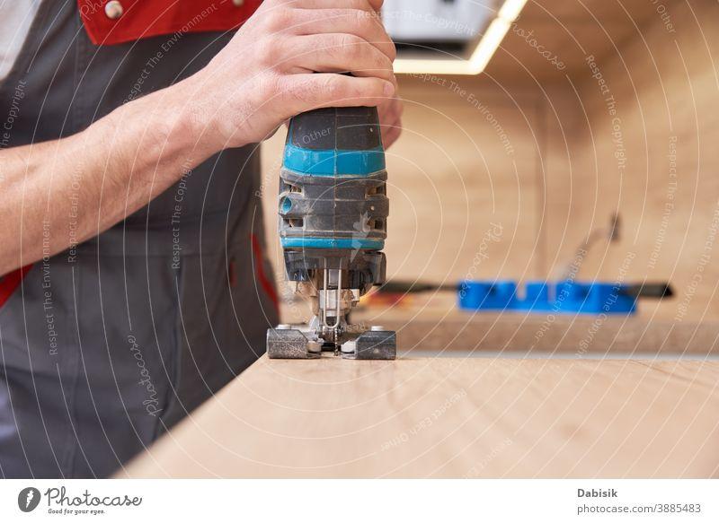 Mechaniker mit elektrischer Stichsäge. Sägeplatz zum Einbau des Gasherdes in die Arbeitsplatte Küche Reparatur Installation passen Konstruktion Einführung
