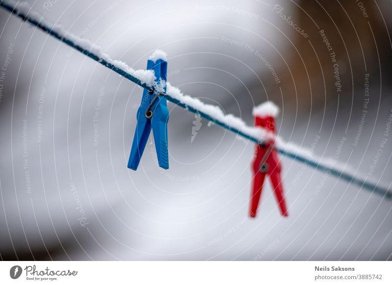 Wäscheklammer an einer Wäscheleine an einem verschneiten Wintertag verschwommen Bokeh Kabel einklemmen pressen Clip schließen Nahaufnahme Kleidung Kleiderspin