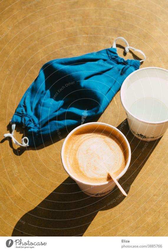 Coffee to go im Pappbecher und mit Maske, weil die Gastronomie wegen Corona geschlossen ist Kaffee take away zum mitnehmen Lockdown light Mundschutz Coronavirus