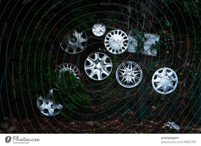 Radkappen-Sammlung an einem Zaun befestigt Autofelgen autozubehör KFZ PKW Verkehr rund Garten silber Schrott Karosserie kaputt alt Außenaufnahme Menschenleer