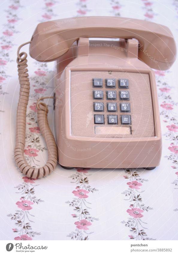 Ein altes Telefon in rosa steht auf einem Tisch mit Blumenmuster. Vintage, fortschritt, Technik, kommunikation vintage tasten Zahlen tapete blumenmuster