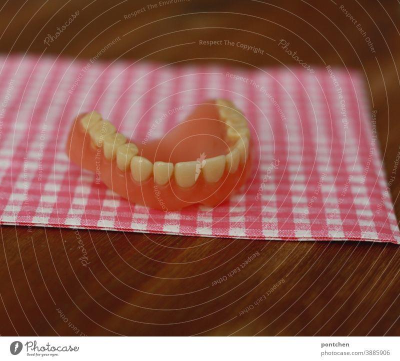 Ein Gebiss liegt auf einer karierten Unterlage. Humor, skuril. Zahngesundheit zahnarzt zahngesundheit senioren altern humor zahnersatz Zähne Künstliche zähne