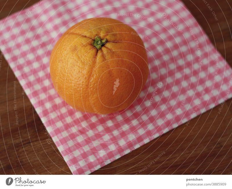 Eine orange liegt auf einer karierten Serviette auf einem Tisch. Vitamin C, gut fürs Immunsystem Orange Zitrusfrucht Gesundheit Frucht Vitamin c frisch Obst