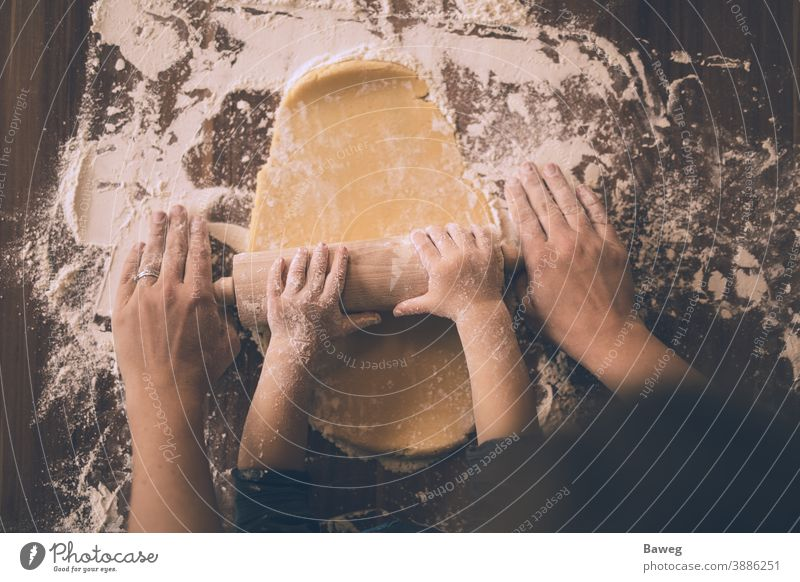 Mutter und Sohn rollen den Keksteig aus. Kind Frau Nudelholz Plätzchenteig Cookies Teigwaren ausrollen rollierend Mehl Waffen Weihnachten Familie Lebensmittel