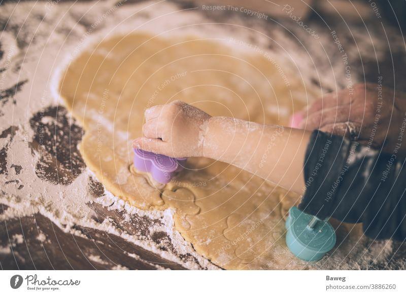Kleinkind schneidet Kekse aus. Kind Junge Küche Ausstechform Plätzchenteig Cookies Kutter Teigwaren Arme Weihnachten Finger Familie Generationen Hand Feiertage