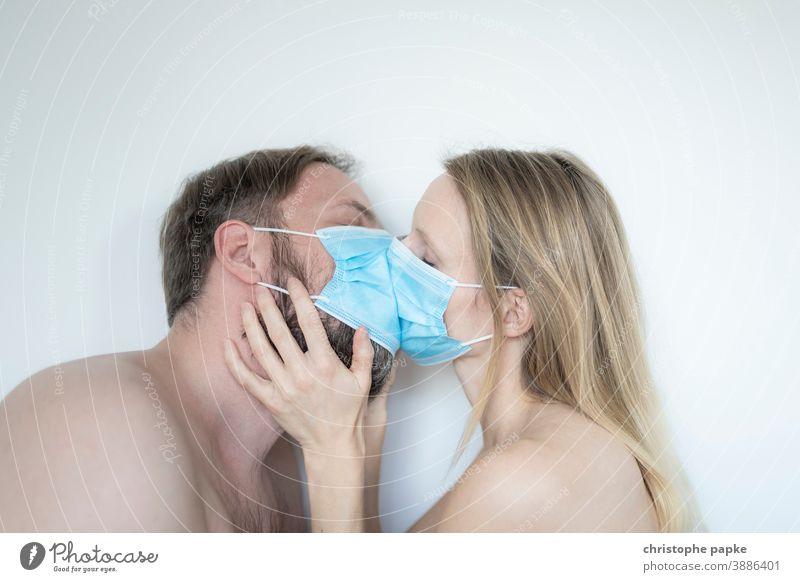 Mann und Frau küssen sich mit Maske mund-nasen-schutz Corona covid-19 COVID Coronavirus Mundschutz Pandemie Corona-Virus Schutz Infektionsgefahr Kuss Schützen