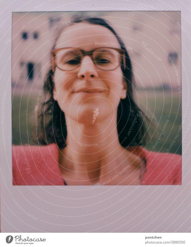 Polaroid-Selfie. Frau mit Brille und braunen Haaren vor einem Haus. Kopf hoch selfie selbstbewusst polaroid lächeln verschmitzt brille Hals gesicht Brünett