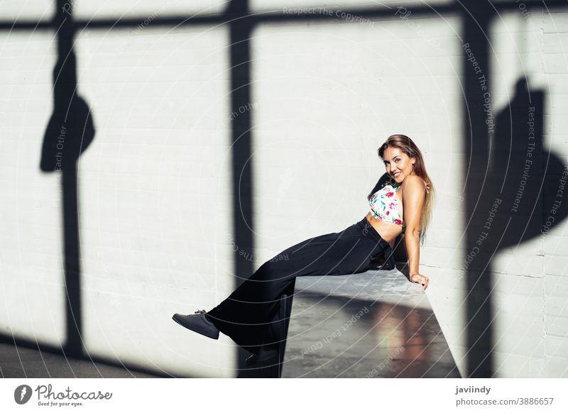 Lustiges junges Mädchen sitzt auf Stadtmauer Frau Person Frisur Behaarung schön Großstadt im Freien Lifestyle Erwachsener urban Stil Glück Straße modern