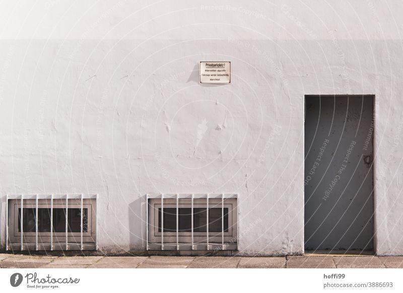 Stahltür und vergitterte Kellerfenster - Privatparkplatz privatparkplatz Warnschild Verbote Parkplatz Vergitterung Tristesse Schilder & Markierungen
