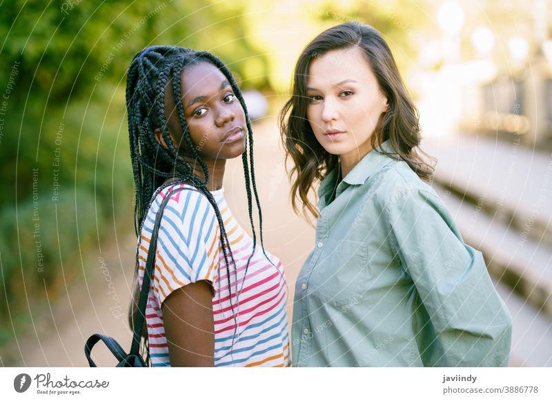 Zwei junge Freunde schauen auf der Straße gemeinsam in die Kamera. Multiethnische Frauen. multiethnisch schwarz Afro-Look Mädchen Schüler zwei Spaß Menschen
