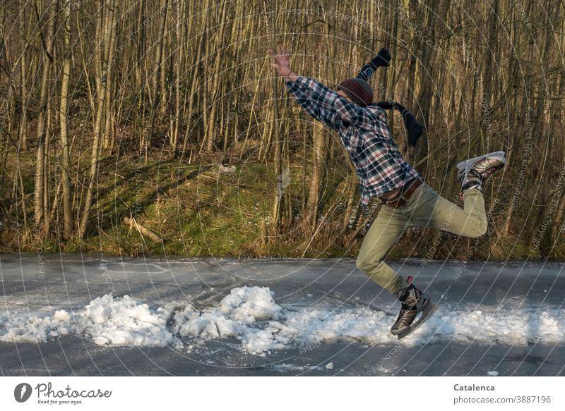 Ab ins Wochenende , junger Mann beim Eislaufen springen Eislaufschuhe Spass Winter Schal Kälte und Frost schnell Freude zugefroren Bäume See sportlich Grau Grün