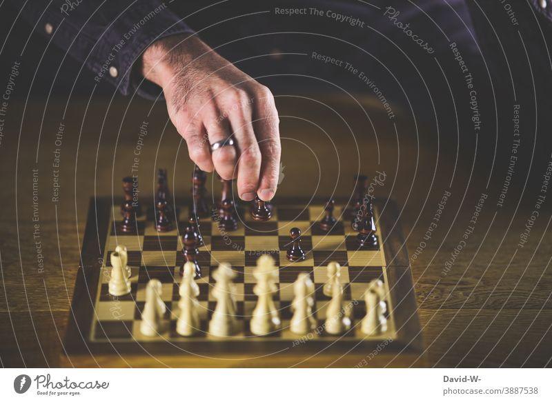 Spieler bewegt eine Schachfigur auf einem Schachbrett nachdenklich Duell angriffslustig Erfolg Geschicklichkeit Taktik Freizeit & Hobby Denken Hand