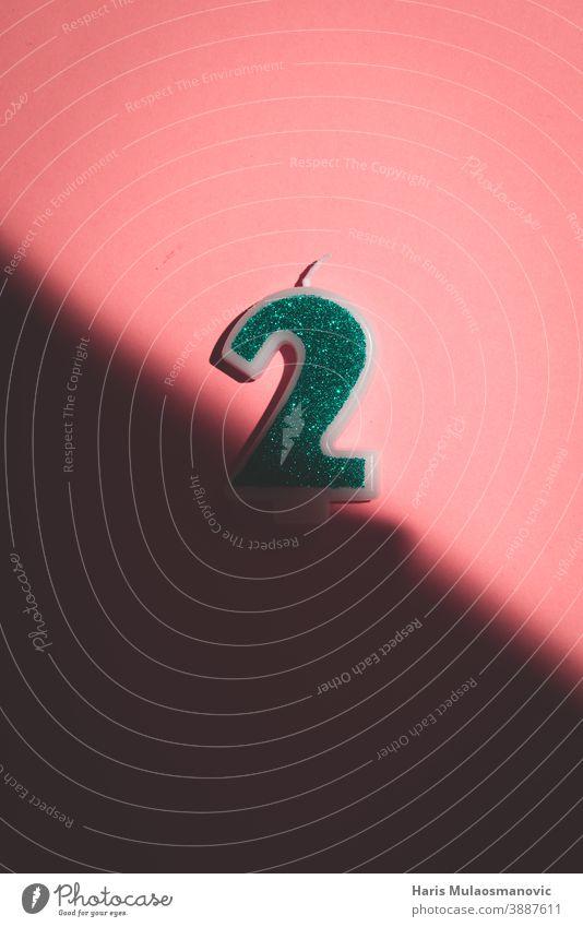 Kerze Nummer 2 auf pastellfarbenem Hintergrund mit Schatten Alphabet Jahrestag Kunst Geburtstag schwarz Postkarte feiern Feier Konzept kreativ