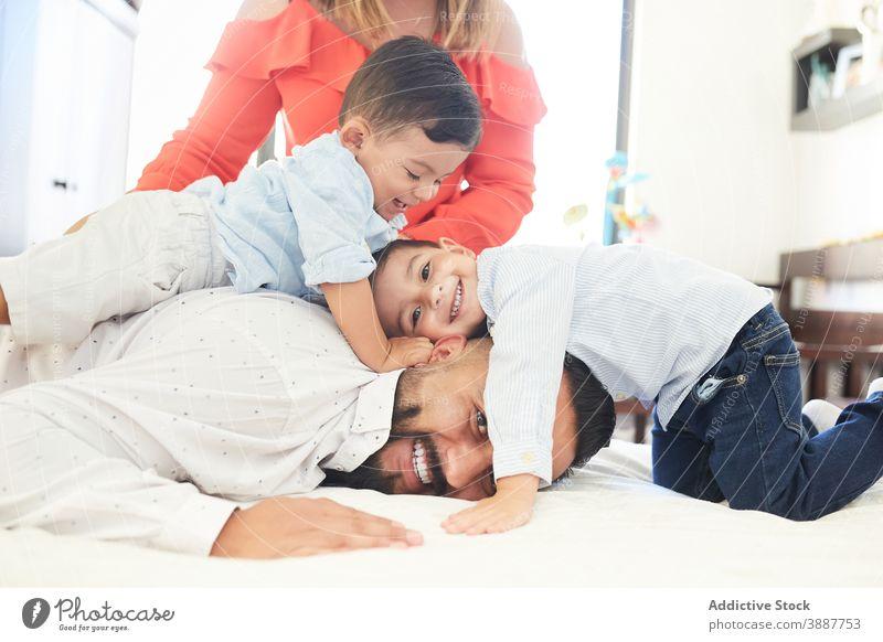 Fröhliche ethnische Familie auf dem Bett zu Hause sich[Akk] sammeln Spaß haben Zeitvertreib Zusammensein Paar Sohn Geschwisterkind heimwärts hispanisch