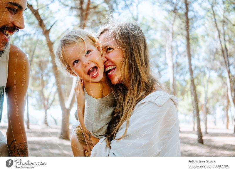 Mutter und Vater kuscheln Kind zusammen Familie Wange Liebe Zusammensein Einheit multiethnisch rassenübergreifend vielfältig Wald Umarmung Angebot Tochter
