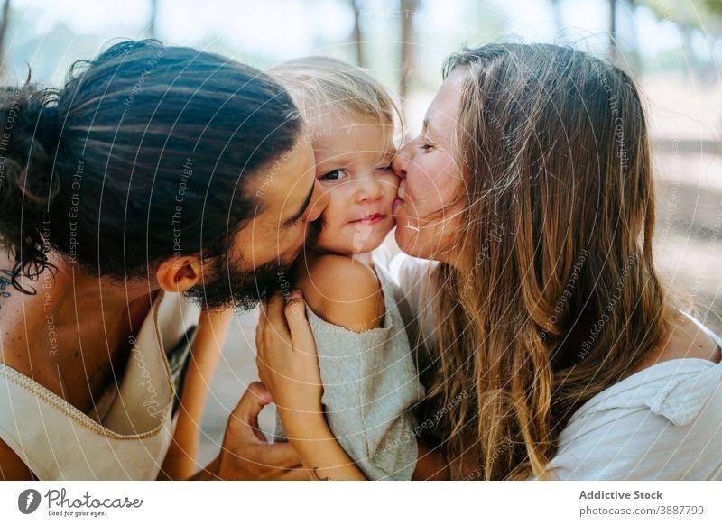 Mutter und Vater küssen Kind zusammen Kuss Familie Wange Liebe kuscheln Zusammensein Einheit multiethnisch rassenübergreifend vielfältig Wald Umarmung Angebot