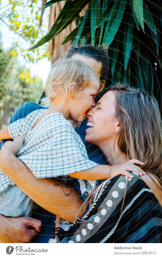 Entzückte Familie umarmt zusammen in tropischen Park Biss Nase Spaß haben Lachen unterhalten heiter Bonden spielerisch Kind Zusammensein Mutter Vater exotisch