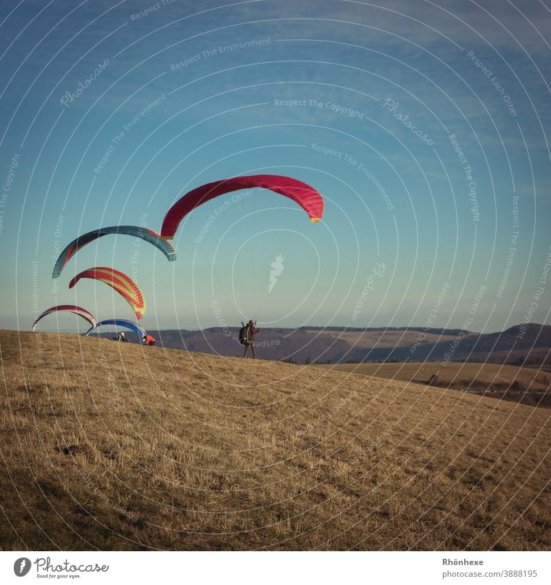 Gleitschirmflieger in der kalten Winterluft auf der Wasserkuppe fliegen Farbfoto Sport oben Himmel mehrfarbig Außenaufnahme Freizeit & Hobby Freiheit Tag