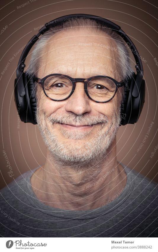 Porträt eines erwachsenen Mannes mit Bart, der einen Stereokopfhörer und eine Brille trägt. Erwachsener attraktiv Audio Vollbart Junge lässig Kaukasier heiter