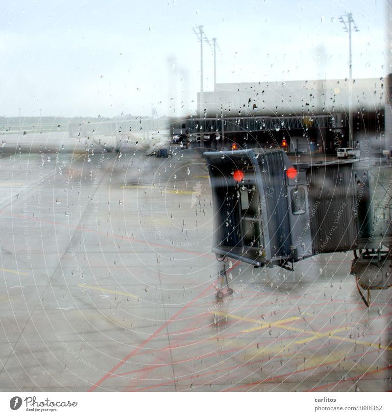 Ab in den Süden| Regentropfen an der Scheibe - Fluggastbrücke in Sicht, aber kein Flugzeug Flughafen Abflug Ankunft Wartezone Wartebereich Fenster grau