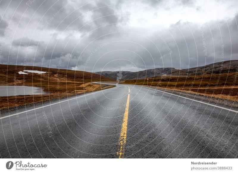 Einsame Landstraße in der Finnmark von Norwegen einsamkeit mystik kurve verkehr fjell gebirge hochgebirge varanger norwegen asphalt gras baumlos steppe abseits