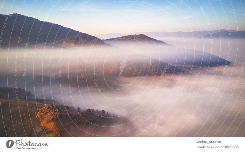 Wunderschönes Bergpanorama im Herbst. Morgens dicker Nebel bedeckt das Tal aus der Vogelperspektive. Fantastischer Sonnenaufgang im Herbst Berge u. Gebirge