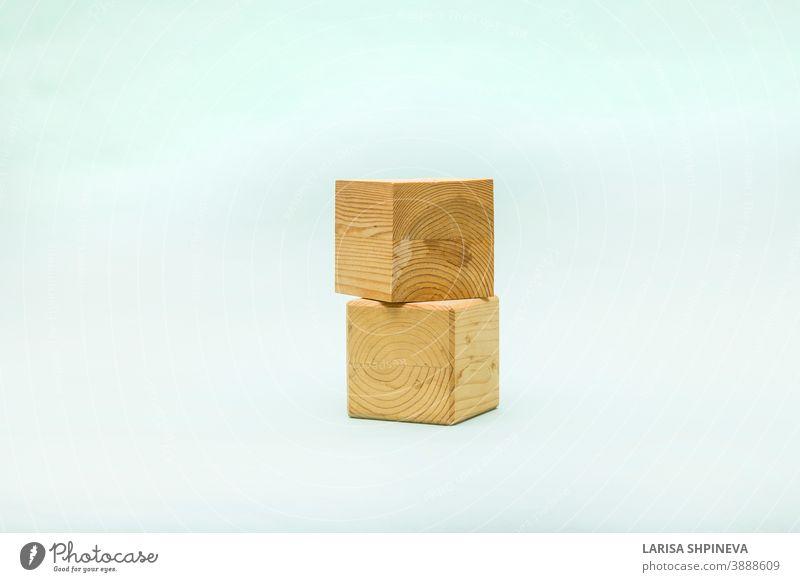 Abstrakter pastellfarbener Hintergrund mit zwei geometrischen Holzformen. Form einer Holzwürfelschachtel für Öko-Produkt. Leere Vitrine im Miniaturstil. Podium
