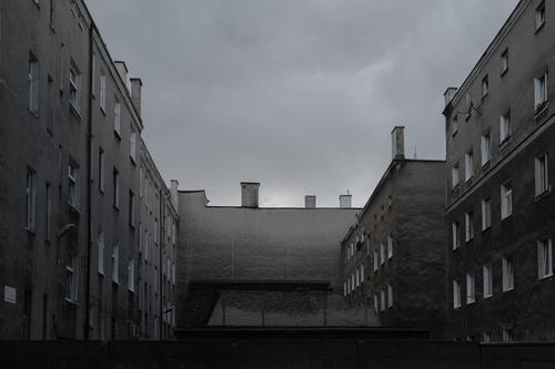 Hausfassaden im Hinterhof – grau und eintönig Gebäude Wohnhaus Mietshaus arm prekär Sozialismus Sozialbau Mehrfamilienhaus trist schäbig heruntergekommen Stadt