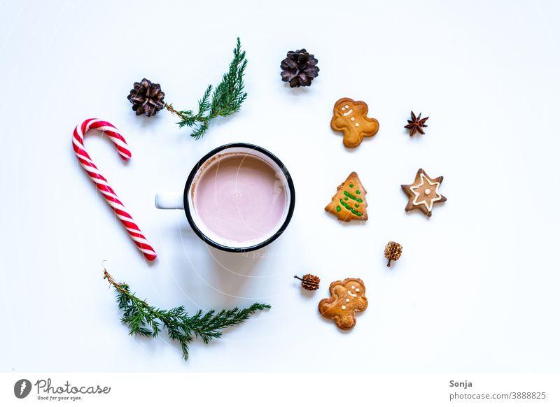 Eine Tasse Kakao mit Lebkuchen Keksen und einer Zuckerstange auf einem weißen Tisch Heißgetränk Weihnachten & Advent Tradition weißer Hintergrund flatlay Winter