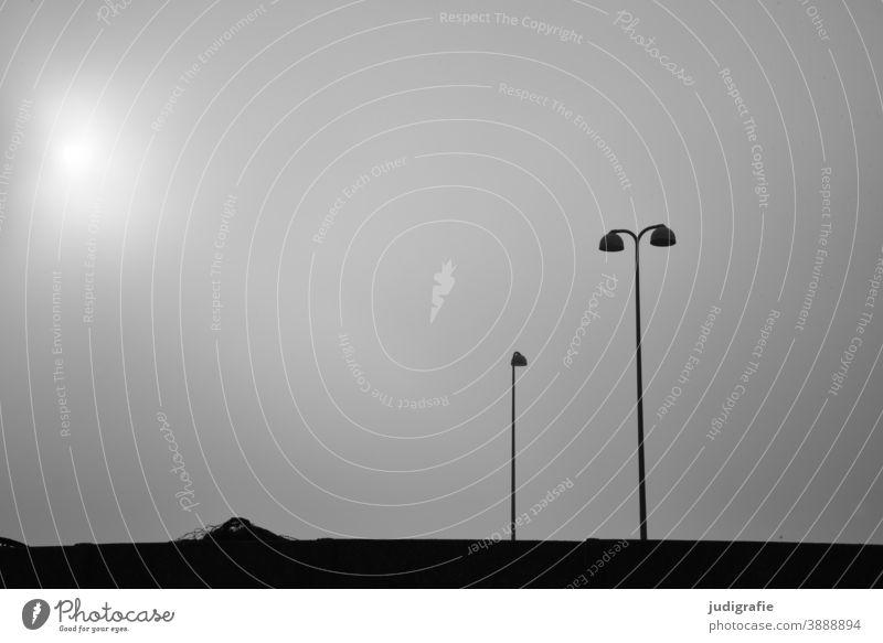 Minimalistische Hafenszene: Straßenlaternen vor dunstigem Himmel Lampe Straßenbeleuchtung Mauer minimalistisch Schwarzweißfoto Monochrom Licht grau Laterne