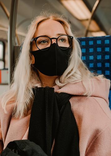 Junge Frau sitzt mit Coronamaske in der Bahn coronavirus junge frau blond lange haare bahn reise gesellschaft winter mantel brille mode style blick hübsch schön