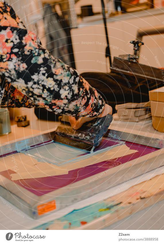 Junge Frau arbeitet in der Siebdruckwerkstatt illustration produktion siebdruck workshop siebdruckwerkstatt kreative kreation handarbeit handcraft brille hübsch