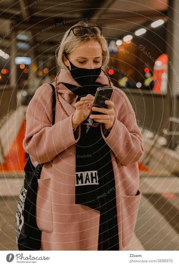 Junge Frau steht am Bahnhof mit einer Koronamaske Coronavirus blond lange Haare Reise Unternehmen Winter Mantel Brille Mode Stil Blick hübsch Porträt Farbfoto
