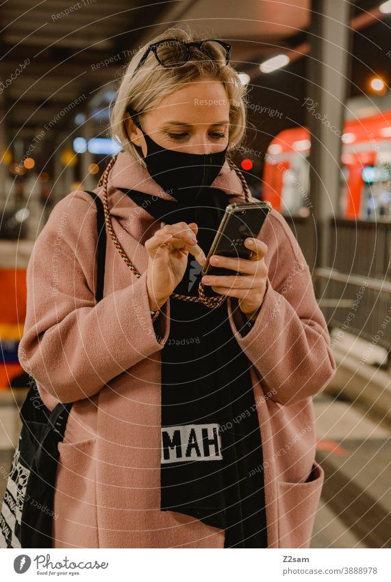 Junge Frau steht mit Coronamaske am Bahnhof coronavirus junge frau blond lange haare bahn reise gesellschaft winter mantel brille mode style blick hübsch schön