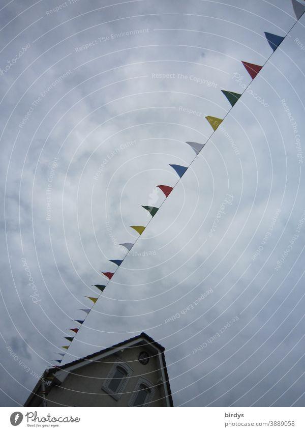 bunte Fähnchen an einer Leine. Straßendekoration Haus Giebelwand, Froschperspektive, bewölkter Himmel, gedeckte Farben Wimpel in einer Reihe