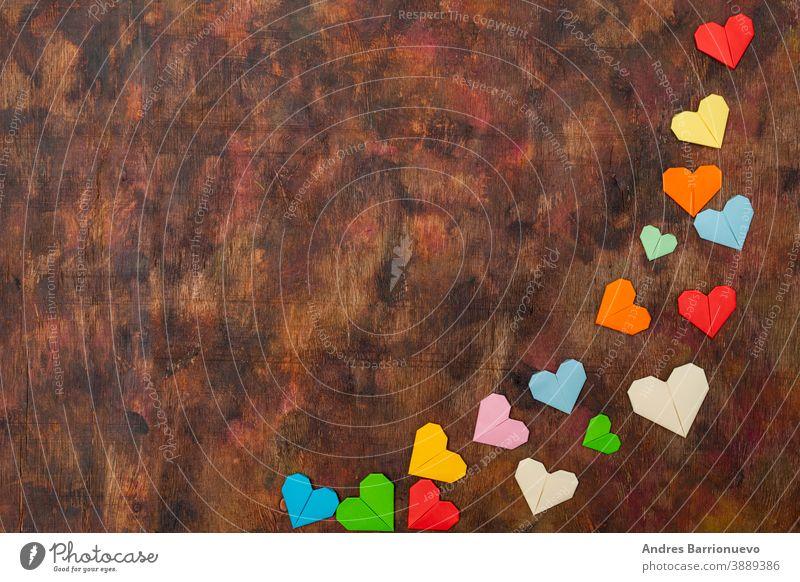 Origami-Herzen aus farbigem Papier zur Gratulation zum Valentinstag für verliebte Paare, auf altem Holzuntergrund in Brauntönen Holzplatte grün hölzern