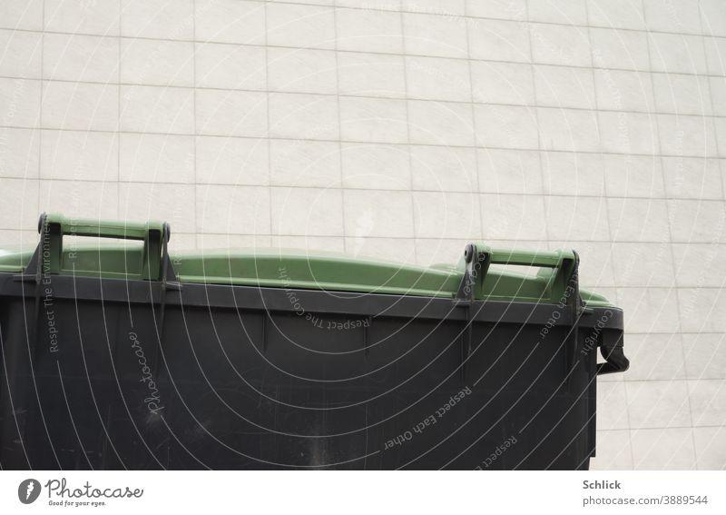 Detail Müllbehälter mit grünem Deckel aus Kunststoff vor heller Fassade mit rechteckigen Fassadenplatten groß hellgrau Rechtecke modern schwarz weiß Griffe