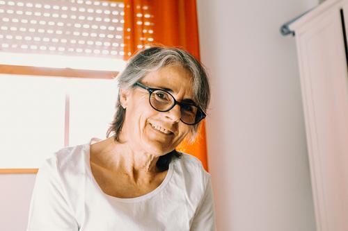 Nahaufnahme einer alten Frau mit Brille lächelnd zur Kamera in einem hellen Schlafzimmer Person Großmutter Dame reif Rentnerin Senior Lächeln Blick Fotokamera