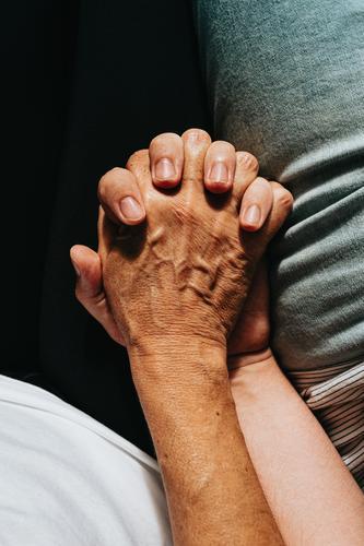 Nahaufnahme einer alten Hand, die eine junge Hand ergreift, auf filmischen Tönen Unterstützung Gemeinschaft Frauen Freundschaft Großeltern Händchenhalten