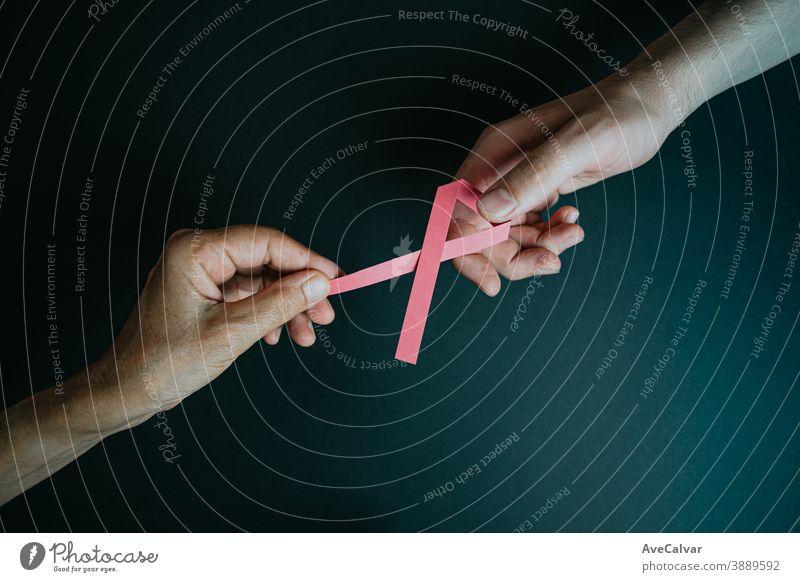 Eine alte Hand gibt einer jungen Hand eine rosa Schleife Erkenntnis Symbol Bändchen Brustkrebs blanko Almosen Kur krank nachschleppend Textfreiraum Überleben