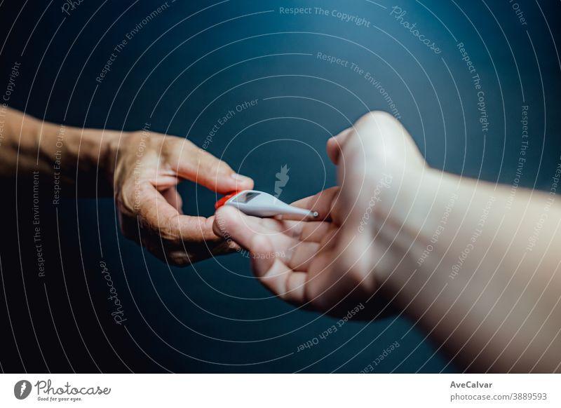 Ein alter Hase gibt einer jüngeren Hand ein Thermometer Grippe Schmerz Krankheit Hemd krank gutaussehend Mode Schmerzen Virus Ganzkörper müde Gesundheitswesen
