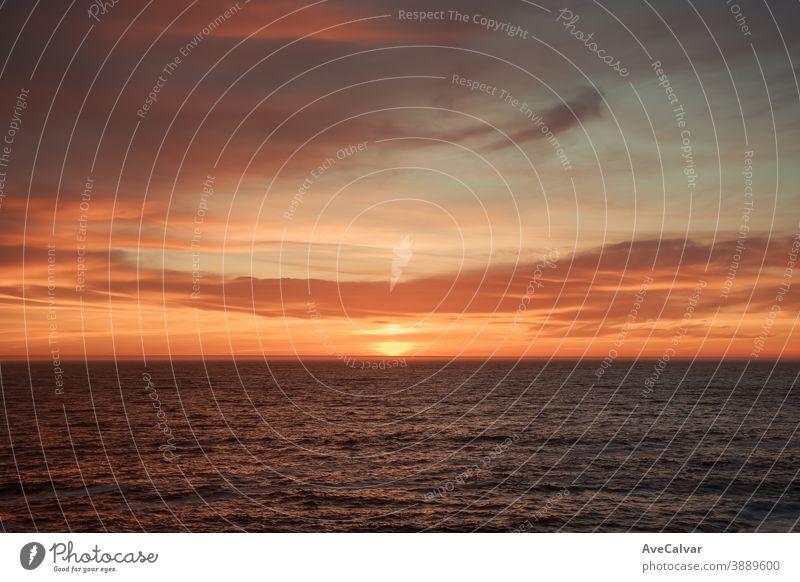 Ein massiver Horizont während eines farbenfrohen Sonnenuntergangs Meereslandschaft beleuchtet im Freien Sonnenlicht Natur Sonnenaufgang szenische Darstellungen