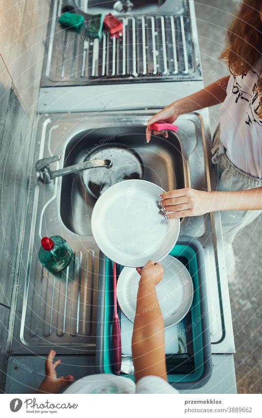 Teenager-Mädchen spült während der Ferien auf dem Campingplatz mit Hilfe ihrer jüngeren Schwester in der Außenküche Töpfe und Teller ab arbeiten Zusammensein