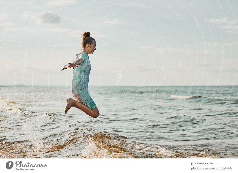 Mädchen, das es genießt, im Sommerurlaub über Wellen zu springen und seine Freizeit am Strand über dem Meer zu verbringen aufgeregt frei genießen positiv