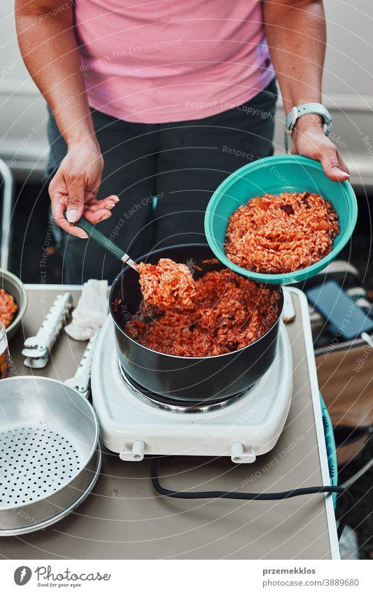 Frau stellt in den Sommerferien auf dem Campingplatz Reisgericht mit Tomatensauce in eine Schüssel Mittagessen Outdoor-Küche heiß Topf Speise Koch Mahlzeit