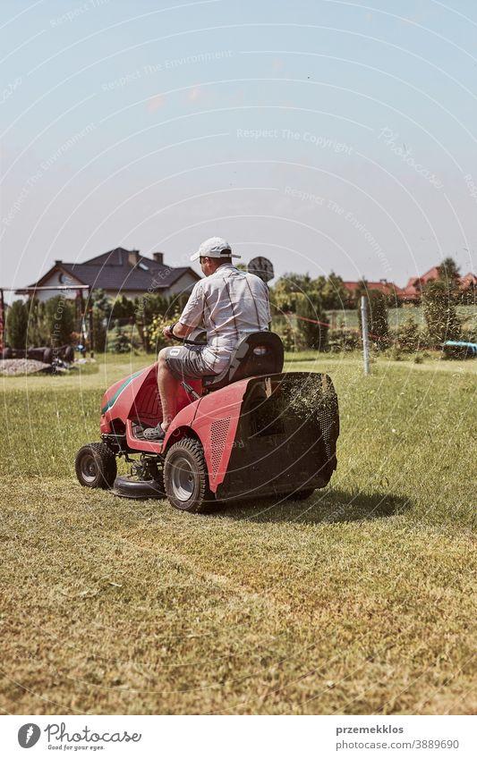 Mann mäht seinen Rasen mit einem Aufsitzrasenmäher Beruf Rasenmäher saisonbedingt geschnitten Trimmen Job Person entgittern Feld professionell