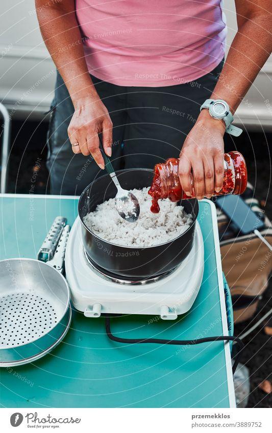 Frau kocht während der Sommerferien auf dem Campingplatz auf einem Elektroherd Reisgericht Mittagessen Outdoor-Küche heiß Topf Speise Koch Mahlzeit im Freien