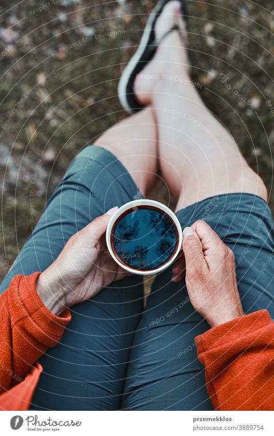 Nahaufnahme einer Frau, die im Freien sitzt und eine Tasse mit Kaffee hält oben Wanderer Ausflug Fernweh Erkundung Lifestyle Picknick Lager Freiheit Urlaub